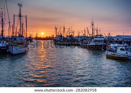 Boats docked at in a shipyard harbor at sunset under hazy pink skies - stock photo