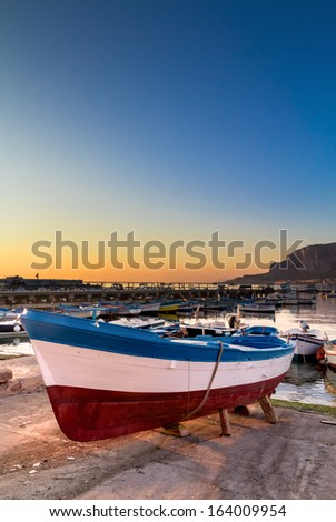 Boats docked in a small harbor in a fishing village on the coast of Sicily at sunset.