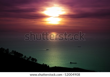 Boats fishing under a beautiful sunset in the sea. - stock photo