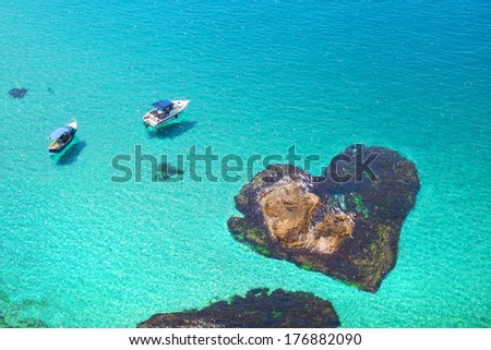 boats floating near the stone in the shape of heart. Romantic island lovers - stock photo