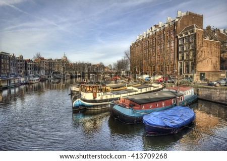 Boats in a canal and buildings in the historical part of Amsterdam, Holland - stock photo