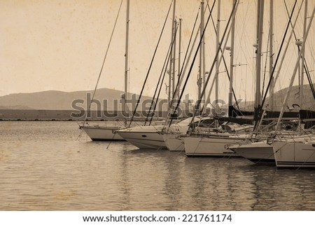 boats in Alghero harbor in vintage tone with stained paper effect - stock photo