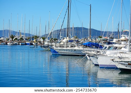 boats in Alghero harbor on a clear day. Shot in Sardinia, Italy - stock photo