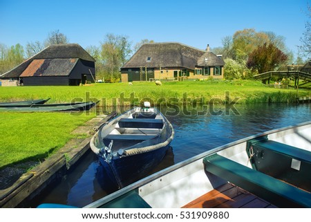 Boats in spring in Giethoorn, a small village in Overijssel province in the Netherlands. Part of the village has no car roads and some houses are accessible by boat only.