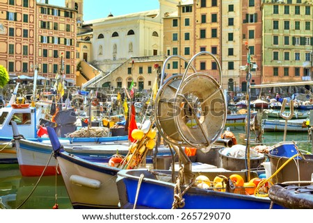 boats in the harbour of the seaport Camogli at the Italian Riviera with a gorgeous colored house facade and luminous shining blue sky - stock photo