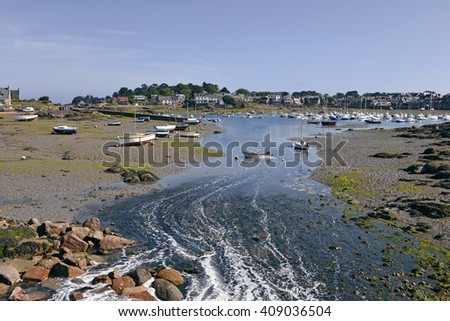 Boats in the port of tregastel on the Pink Granite Coast (cote de granite rose in french) with Ploumanach in the background. Tregastel is a commune in the Cotes of Armor in northwestern France