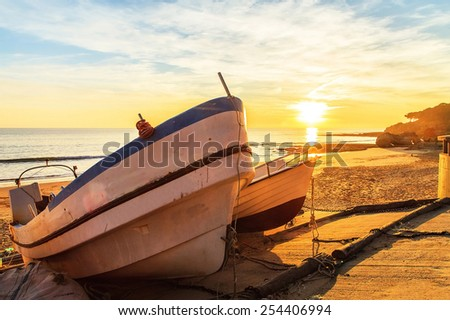 Boats in warm sunset light on the majestic beach - stock photo