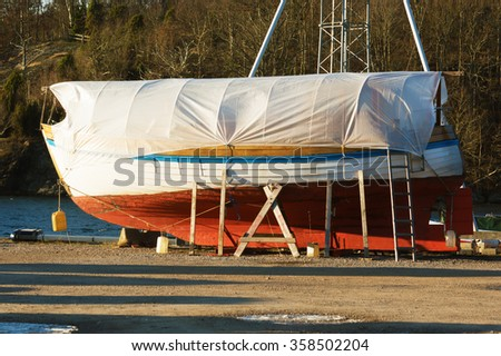 Boats in winter storage covered with tarps and supported by scaffolding. Winter storage on land protects the boats from the sea ice that could otherwise cause damage to the keels. - stock photo