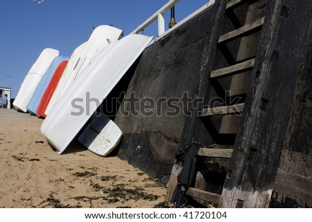 Boats leaning up on harbour wall with wooden ladder, Broadstairs - stock photo
