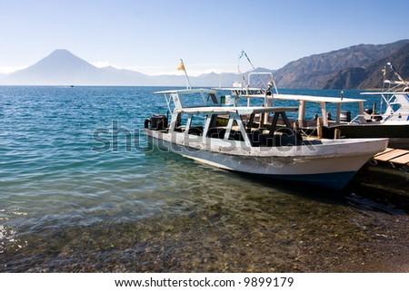 Boats moor alongside the jettys out into Lake Atitlan - stock photo