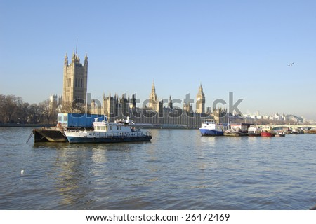 Boats moored on the River Thames in front of the Houses of Parliament, London, England - stock photo