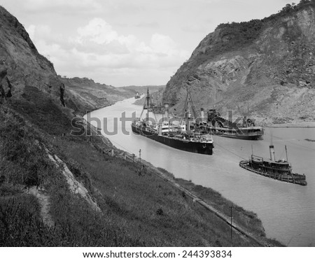 Boats move through Panama Canal at the Culebra Cut (Gaillard Cut), which crosses the continental divide. At center right is a suction dredge to maintain canal depth. Ca. 1910-14. - stock photo