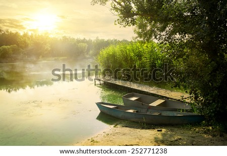 Boats near pier at beautiful summer morning - stock photo