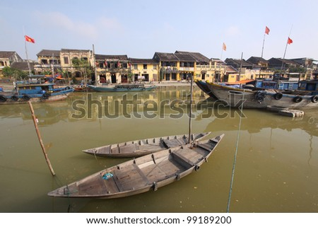 Boats of fishing and transportation in Tu-bone river with yellow old town behind. Hoi An, Central Vietnam - stock photo