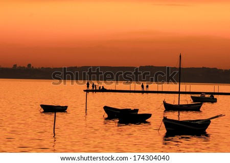 Boats on lake silhouettes at sunset - stock photo