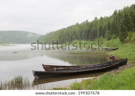 Boats on river in fog near forest