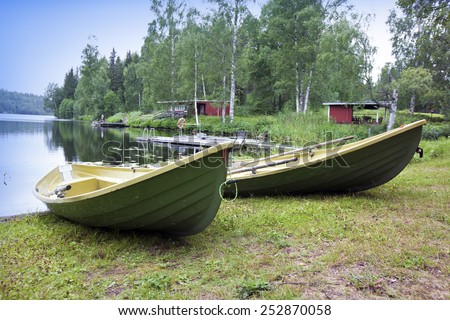 Boats on the bank of the forest lake - stock photo