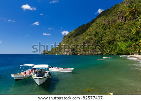 Boats on the clear waters of a beach in Soufriere in St Lucia - stock photo