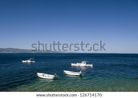 Boats on the sea, beach and mountains in Omis