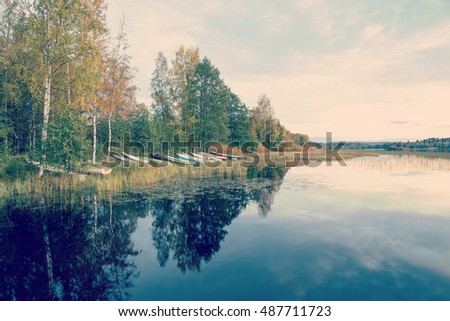Boats on the shore on an autumn evening. Water is reflecting the boats and the forest. Beautiful sky. Image has a vintage effect applied. Image taken in Finland.