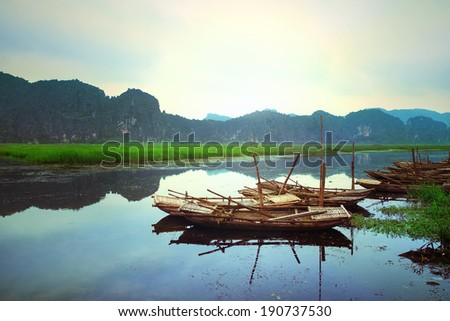 Boats on Van Long Natural Reserve (Ninh Binh, Vietnam) in the fog