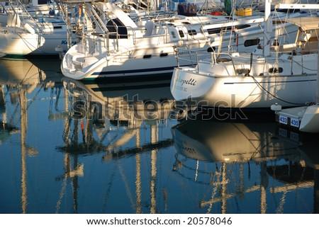 Boats reflected in marina - stock photo