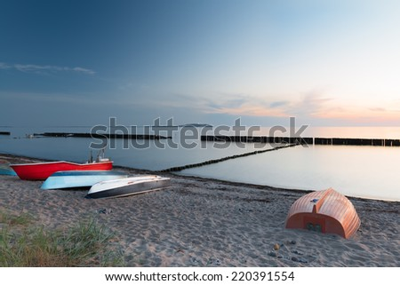 Boats resting on sandy beach in the evening