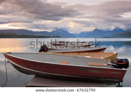 Boats sit on the dock at Lake McDonald at sunset.  Glacier National Park, Montana. - stock photo