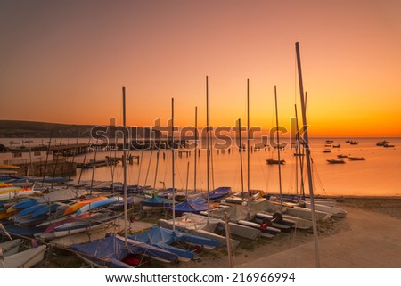 Boats, the new and old piers are illuminated by the orange pre-dawn - stock photo