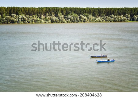 Boats with fishermen at the river Danube. - stock photo