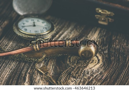 Boatswain's whistle and pocket clock on the wooden table.