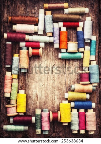 bobbins with colorful threads on old wooden table background - stock photo