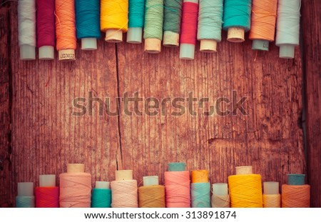 Bobbins with colorful threads on old wooden table background, Sewing background - stock photo
