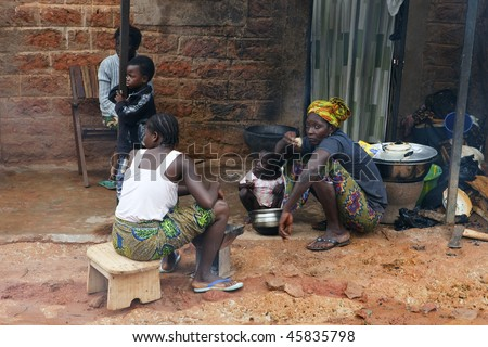 BOBO DIOULASSO, BURKINA FASO - AUGUST 14: Women and children have meals at the entrance of a house August 14, 2009 in Bobo Dioulasso, Burkina Faso. Bobo Dioulasso is the 2nd largest city in the country.