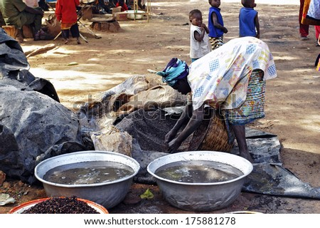 BOBO-DIOULASSO, BURKINA FASO - DECEMBER 31: an old woman cooking local beer made from millet in Burkina Faso called Dolo in the middle of a street in Bobo-Dioulasso, december 31, 2007 - stock photo
