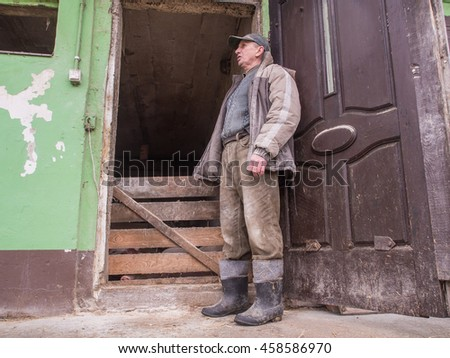 Bobrek , Poland - February 10, 2016: A polish farmer standing in front of a pigstay