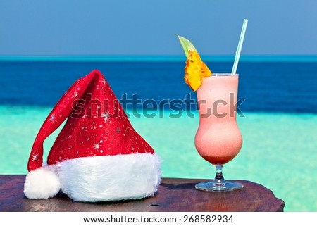 Bocal of drink is on a beach table with Santa hat (Maldives, The Indian Ocean) - stock photo