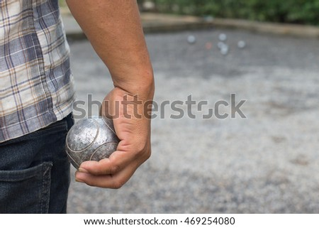 Bocce ball in the hands of men.The men were playing petanque