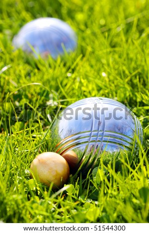 Bocce balls on a green grass. Close up with shallow dof. - stock photo