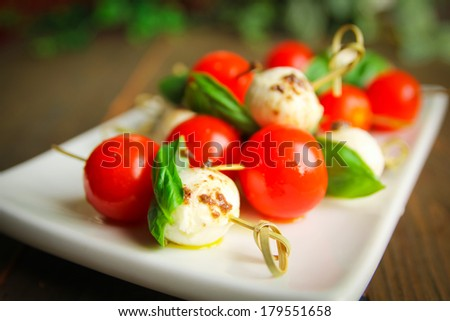 Bocconcini with basil and cherry tomatoes on skewer - stock photo