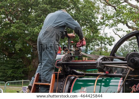 BOCONNOC, CORNWALL, ENGLAND, UK - JULY 31, 2016: Man Pouring Oil into Old Industrial Steam Engine. Historic Heritage Concept. Editorial Use Only
