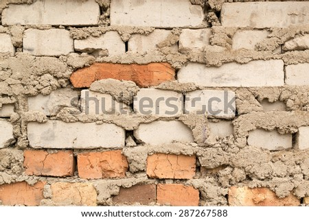 Bodged brick wall with messy loose cement - stock photo