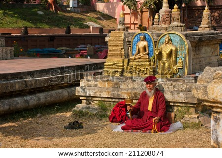 BODH GAYA, INDIA - JAN 9: Old man in dress of monk sitting and praying on January 9, 2013. Bodh Gaya is 1 of 4 pilgrimage sites related to the life of Buddha, with Kushinagar, Lumbini, and Sarnath - stock photo