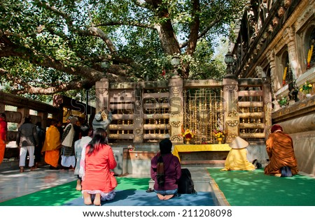 BODH GAYA, INDIA - JAN 9: Women and men sitting on the floor and watching the Bodhy tree, where Buddha attained enlightenment on January 9 2013. It is one of the 4 holy sites related to life of Buddha - stock photo