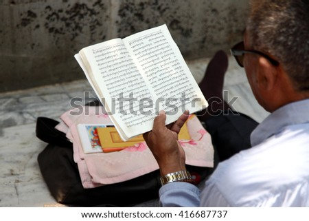 BODH GAYA, INDIA - MAR 08: Unidentified Buddhist reads the holy text at Mahabodhi Temple on March 08, 2016 in Bodh Gaya, India. Its a UNESCO World Heritage site known for enlightenment of Buddha.