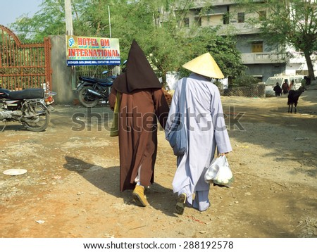 Bodhgaya, India, Dec 17, 2012. Two Buddhist pilgrims in traditional Asian costume walk to their hotel