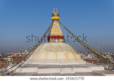 Bodhnath (Boudhanath) Stupa with Brightly Colored Prayer Flags, hoisted at Losar (Tibetan New Year), Kathmandu, Nepal. Below the Eyes of Buddha pigeons rest on the dome. - stock photo