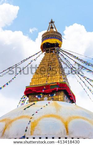Bodhnath stupa in Kathmandu with buddha eyes and prayer flags on clear blue sky background, Nepal 2014 - stock photo