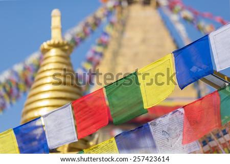 bodhnath stupa in kathmandu with buddha eyes and prayer flags with clear blue sky  - stock photo