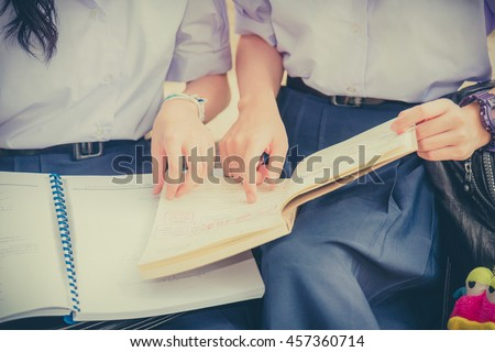 Body and hands of cute Asian Thai high schoolgirls student couple in school uniform discussing homework or education exam together with books in vintage childhood (Focus on models finger and bool). - stock photo